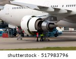Stock photo engine of passenger jet aircraft with open hoods closeup engineers and technicians repair the 517983796