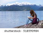 girl sitting on a fjord coast... | Shutterstock . vector #518590984