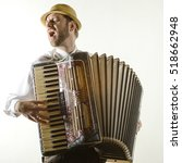 Small photo of Portrait of professional musician with accordion at white wall