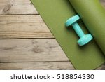 dumbbell and yoga mat on wood... | Shutterstock . vector #518854330
