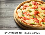 margarita pizza at wooden table | Shutterstock . vector #518863423