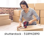 Small photo of Beautiful girl is packing a moving box using an adhesive tape looking at camera and smiling