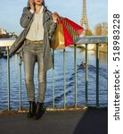 Small photo of Get your bags ready for the Paris autumn sales. young fashion-monger in sunglasses with shopping bags speaking on a mobile phone near Eiffel tower