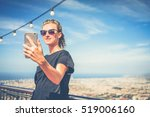 Small photo of Summer sunny day.Smiling girl in sunglasses,black T-shirt,standing outdoors and holding smartphone.In background view of Barcelona from Mount Tibidabo.Woman using gadget,chatting,browsing internet