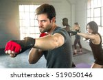 Handsome masculine athlete boxer mma fighter training with fitness group punching aerobox
