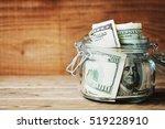 Dollar Bills In Glass Jar On...