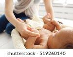 mother massaging her newborn... | Shutterstock . vector #519260140
