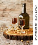 Small photo of Italian liqueur Amaretto in cups with almonds on a wooden table, selective focus