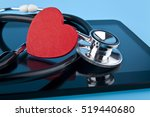 stethoscope, heart and tablet on blue background closeup