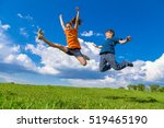 Two Happy Kids Jumping On Gree...