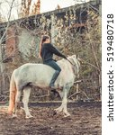 Small photo of Young beautiful brunette girl rides a horse bareback with hackamore. Warm and sunny autumn day. Portrait of a pretty young woman on the horse, wearing tall boots and gloves.