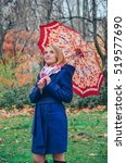 Small photo of Autumn portrait of the woman in leaves with umbrella. Beautiful fashionable girl in the fall under parasol