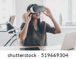 Stock photo future is right now confident young woman adjusting her virtual reality headset and smiling while 519669304