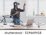 Stock photo innovation in business confident young woman in virtual reality headset pointing in the air while 519669418