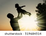 Small photo of happy parent father with baby silhouette in a park on the nature of the sunset