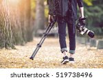 professional photographer with camera and tripod in autumn. Vintage tone. - stock photo