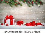 Christmas wood background with a white gift box, red bow and ribbon, baubles, fir branches and snow - stock photo