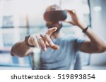 Stock photo closeup of male hand bearded young man wearing virtual reality goggles in modern coworking studio 519893854