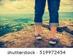 Small photo of Closeup of tourist's feet on boulder at view point on summer day. Woman hiking accomplishment on the top of the mountain. Motivation and freedom concept. Cross process and vintage tone effect.