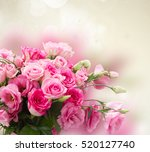 Stock photo bunch of pink roses and eustoma flowers with copy space on gray bokeh background 520127740
