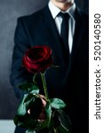 Stock photo close up of man in black suit holding red rose 520140580