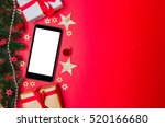 Smartphone in Christmas red background view with tree, gift and decoration - stock photo