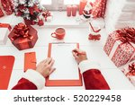 Santa Claus Working At Desk An...