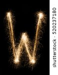 Small photo of English big Letter W made from burning sparkles on black background. Shiny festive party firework font, latin alphabet text sign.
