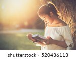 asian girl reading book at park ... | Shutterstock . vector #520436113