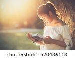 asian girl reading book at park ... | Shutterstock . vector #520436113