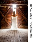 Small photo of Bride standing in door way facing away with mr. and mrs burlap sign above her head in a rustic setting.
