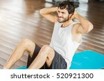 man working out his abs in a gym | Shutterstock . vector #520921300