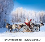 Stock photo santa claus are near his reindeers in snowy forest 520938460