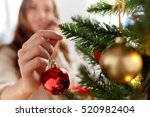 Small photo of x-mas, winter holidays and people concept - happy young woman decorating christmas tree with ball at home