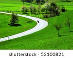 Motorbike rider in a street curve in a rural landscape - stock photo