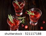 Small photo of Christmas refreshing alcoholic drink with cranberries and rosemary on wooden background, with fir branches