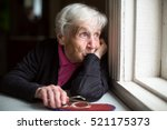 an elderly woman looks sadly... | Shutterstock . vector #521175373