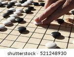 Small photo of Close up view of hand playing black and white stone pieces on Chinese go game board. Outside activity with natural sun light.