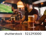Stock photo closeup of three young men sdrinking beer in bar and watching football match 521293000