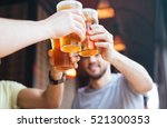 Stock photo happy male friends clinking with beer mugs in pub 521300353