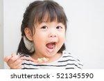 happy little asian girl eating... | Shutterstock . vector #521345590
