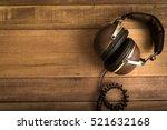 headphones on wooden background | Shutterstock . vector #521632168