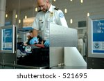 A TSA agent searches luggage at an airport. (12MP camera, NO model release, editorial only) - stock photo