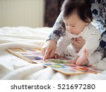 asian baby girl reading book... | Shutterstock . vector #521697280