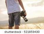photographer holding his camera.... | Shutterstock . vector #521853430