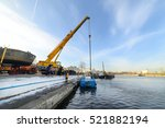 Small photo of MOSCOW, RUSSIA - NOVEMBER 11, 2016: State Unitary Enterprise Mosvodostok performs recovery vessels on coastal winter parking. Powerful truck crane vessel begins to rise out of the water.