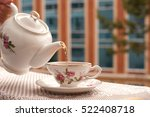 Small photo of Tea in the tea service on the balcony. Tea is poured from a teapot into a cup. Cup of tea elegant. Tea on a gentle kitchen towel creates coziness. Added warm tone.