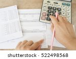 Small photo of hand checking document monthly expense of credit card with passbook bank and payment slip of bank