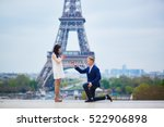 Small photo of Romantic engagement in Paris, man proposing to his beautiful girlfriend near the Eiffel tower. Surprise proposal or elopement concept