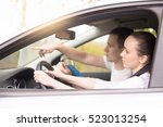 Small photo of Lifestyle side view portrait of young woman driving instructed by a more skilled driver or coacher, analyzing traffic conditions, performing task